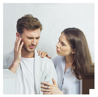 férfi fogja a fülét, mellette nő aggódó tekintettel áll